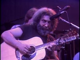 Screenshot of Jerry on acoustic guitar from the Grateful Dead Dead Ahead DVD.